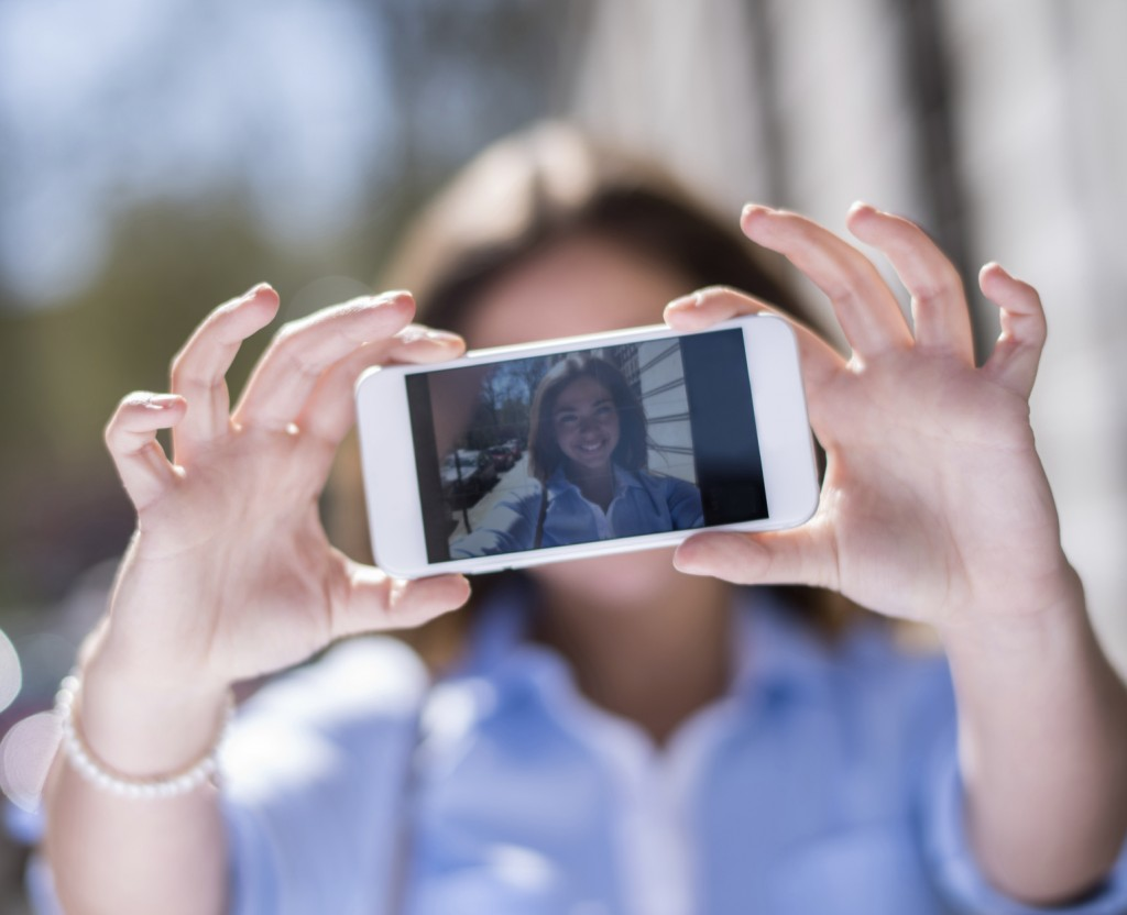 Young woman taking a selfie on the street with a cell phone and showing the picture to the camera on the display